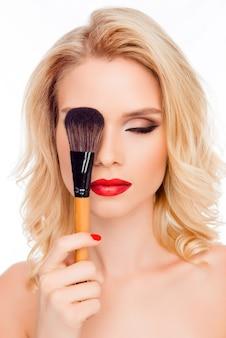 Sexy vrij blonde verbergend oog achter make-upborstel