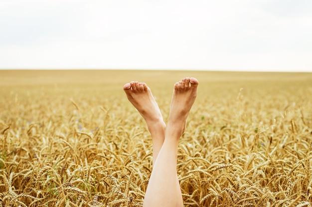 Sexy vrouw benen op blauwe hemel en tarwe veld achtergrond zomer vakantie concept ontspannen op een zonnige ...