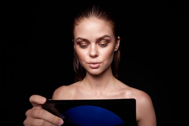 Sexy vrouw blote schouders schone huid natte haren donkere achtergrond. hoge kwaliteit foto