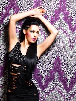 Sexy vrouw danseres met lichte make-up vormt op creatieve paarse achtergrond