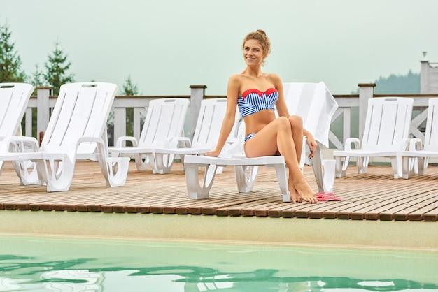 Sexy vrouw die de zomer van vakantie geniet dichtbij pool bij toevlucht.