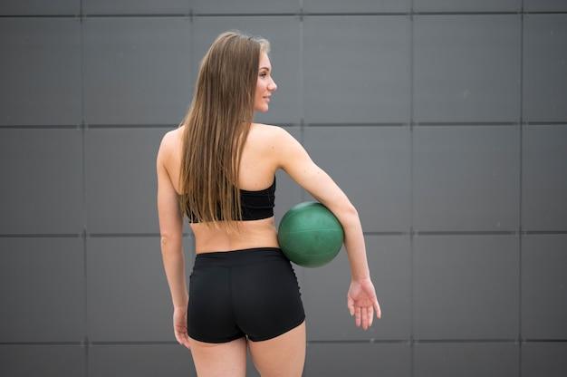 Sexy vrouw die geschiktheid in het middelgrote schot van het stadspark doet