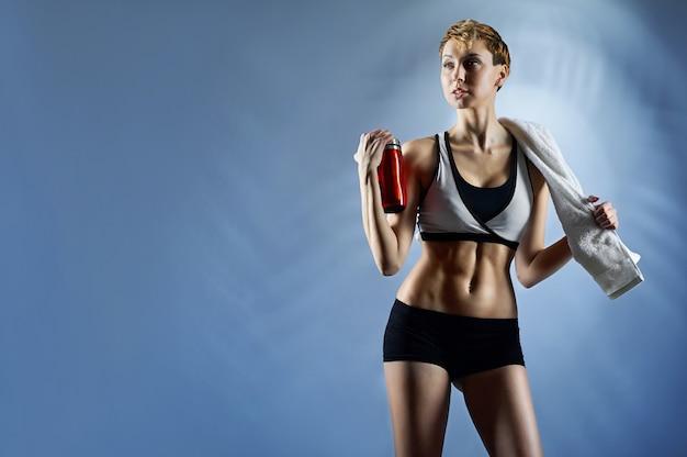 Sexy vrouw die sportenbovenkant en borrels draagt