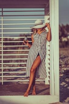 Sexy vrouw draagt lange linnen gestripte jurk en hoed met gebruinde huid en perfect figuur staat vlakbij het strand