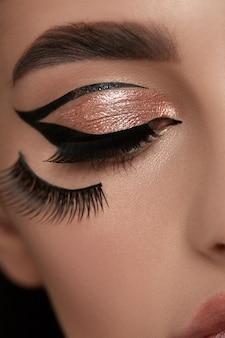 Sexy vrouw eyeliner met gouden schaduw en wimpers