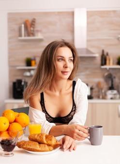 Sexy vrouw genieten van warme koffie tijdens het ontbijt in de keuken sexy ondergoed dragen.