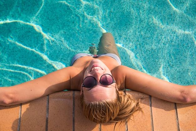 Sexy vrouw in bikini genieten van zomerzon en bruinen tijdens vakantie in het zwembad. bovenaanzicht. vrouw in zwembad. sexy vrouw in bikini.