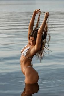 Sexy vrouw in een badpak aan de rivieroever