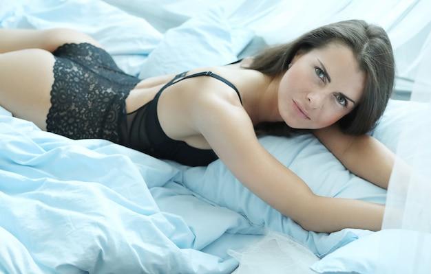 Sexy vrouw in lingerie liggend op het bed