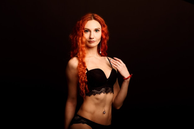 Sexy vrouw in lingerie op zwarte achtergrond, rood haar