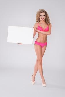 Sexy vrouw in ondergoed met whiteboard