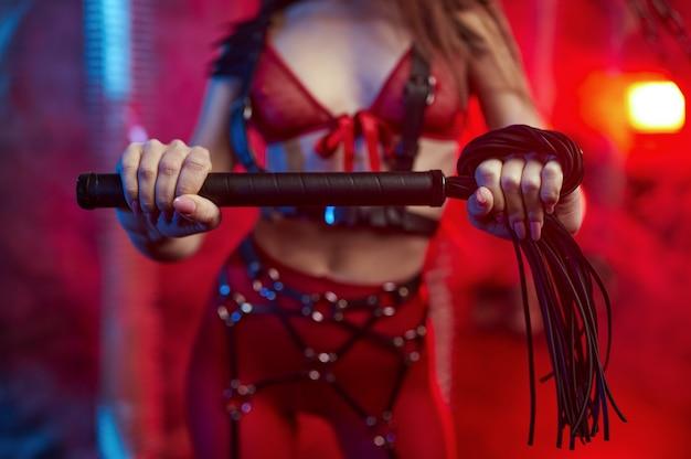 Sexy vrouw in rood bdsm-pak houdt lederen zweep, verlaten fabrieksinterieur. jong meisje in erotisch ondergoed, sexfetisj, seksuele fantasie
