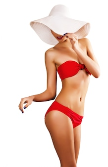 Sexy vrouw in rood zwempak en witte hoed