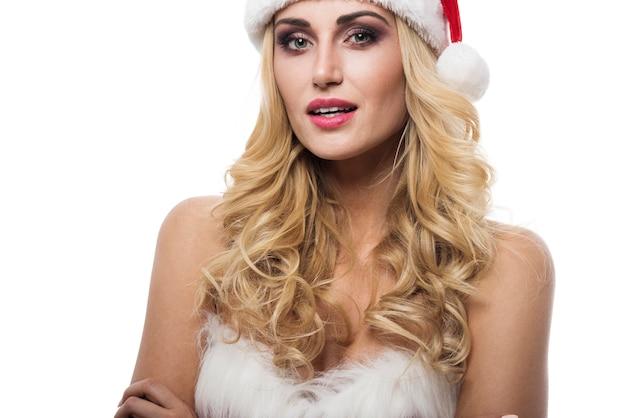 Sexy vrouw in santa kostuum poseren op witte muur