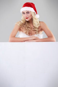 Sexy vrouw in santakostuum op grijze muur