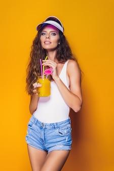Sexy vrouw in wit zwembroek en spijkerbroek korte broek, trendy vizier met glas vers drankje terwijl staande op geel, oranje heet