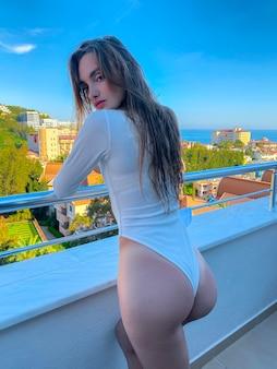 Sexy vrouw in witte romper staat op een balkon met uitzicht op zee op background