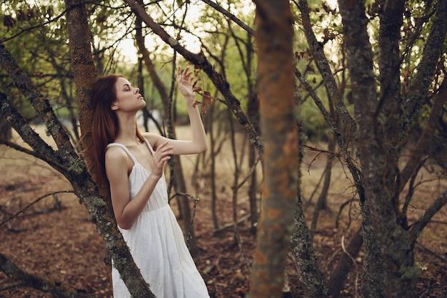 Sexy vrouw in witte zomerjurk in de buurt van bomen in de tuin.