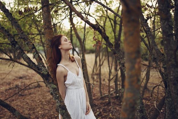 Sexy vrouw in witte zomerjurk in de buurt van bomen in de tuin