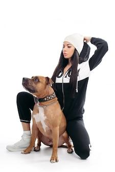 Sexy vrouw in zwart pak en witte hoed met hond.