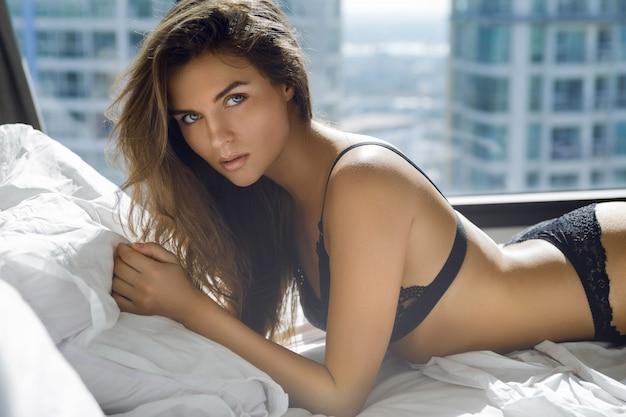 Sexy vrouw in zwarte lingerie liggend op het bed