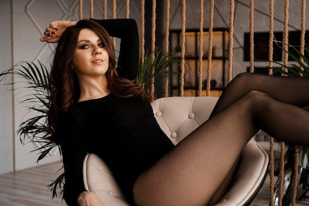 Sexy vrouw in zwarte panty zittend op de stoel - ontspan thuis