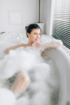 Sexy vrouw liggend in bad met schuim, ontspanning in luxe badkamer met stenen decor