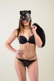 Sexy vrouw met catwoman-vermomming, masker, verleidelijk ondergoed, studio