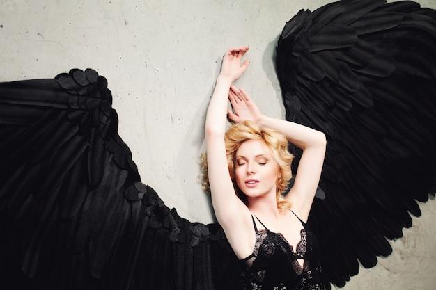 Sexy vrouw met engelenvleugels ontspannen op de vloer