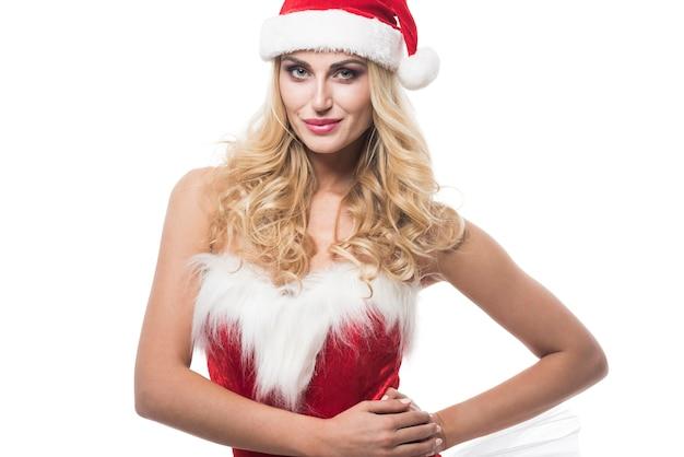 Sexy vrouw met kerstmuts poseren op witte muur