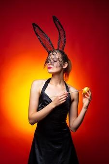 Sexy vrouw met konijntjesoren op rode achtergrond. pasen vakantie concept. portret van charmante vrouw close-up.