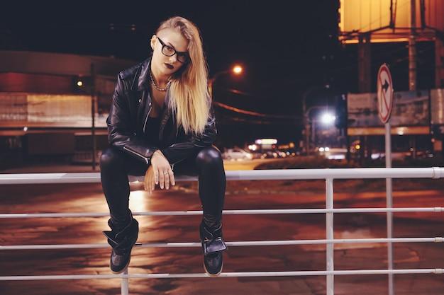 Sexy vrouw met lang haar in lederen kleding op nacht stad straat