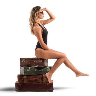 Sexy vrouw met zwembroek zittend op koffers