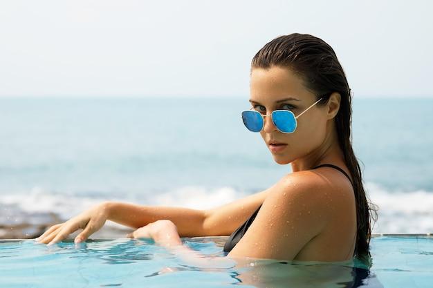 Sexy vrouw ontspannen in het zwembad tijdens haar zomervakantie