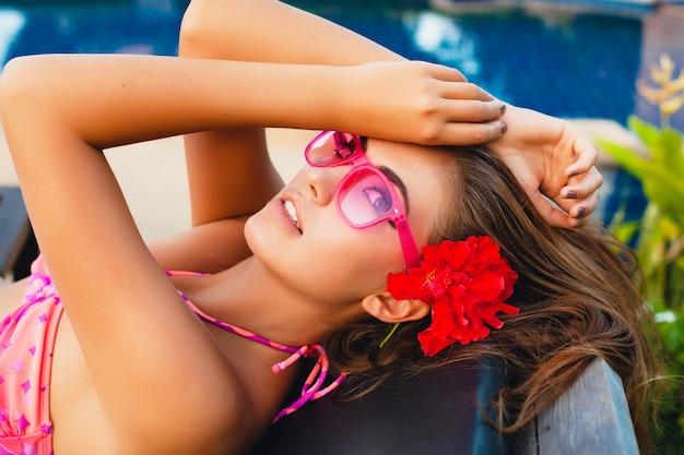 Sexy vrouw op zomervakantie liggend bij zwembad dragen van bikini en roze zonnebril, tropische bloemen, kleurrijke zomer mode-stijl