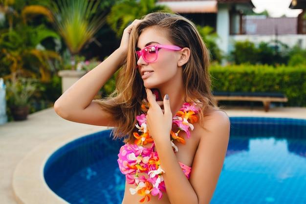 Sexy vrouw op zomervakantie plezier bij zwembad dragen van bikini en roze zonnebril, tropische bloemen, kleurrijke zomer mode-stijl