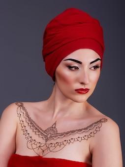 Sexy vrouw poseren in de studio, rode lippen, geïsoleerde violet blauwe achtergrond, henna tatoeage op de borst
