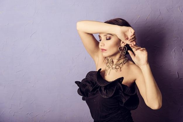 Sexy vrouw poseren in zwarte jurk.