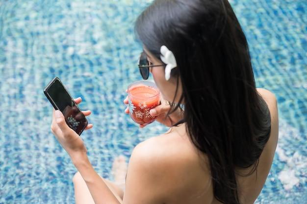 Sexy vrouw spelen smartphone bij zwembad