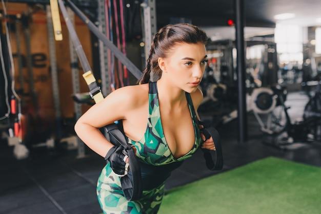 Sexy vrouw training armen met trx fitness riemen in de sportschool doet push ups trainen bovenlichaam borst schouders pecs triceps.