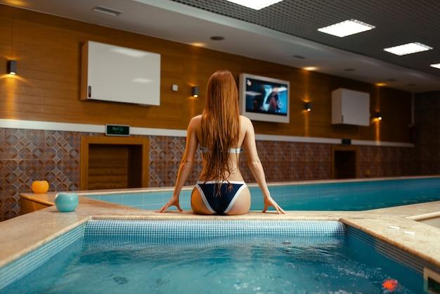 Sexy vrouw uit het water in zwembad binnenshuis, achteraanzicht.