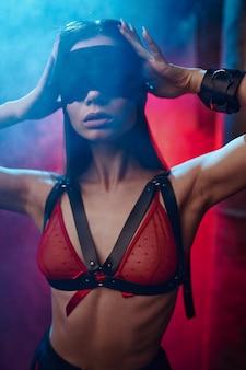 Sexy vrouw vormt in bdsm blinddoek en handboeien, verlaten fabrieksinterieur. jong meisje in erotisch ondergoed, sexfetisj, seksuele fantasie