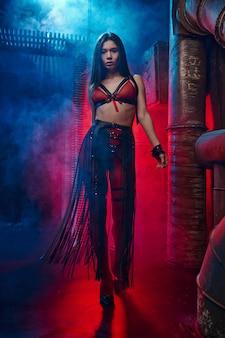 Sexy vrouw vormt in lederen bdsm pak, verlaten fabriek interieur. jong meisje in erotisch ondergoed, sexfetisj, seksuele fantasie