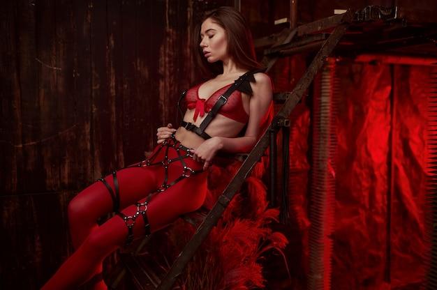 Sexy vrouw vormt in rood bdsm-pak, verlaten fabrieksinterieur. jong meisje in erotisch ondergoed, sexfetisj, seksuele fantasie