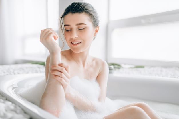 Sexy vrouw wrijft het lichaam met schuim in het bad