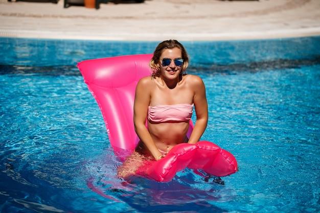 Sexy vrouwelijk model in zonnebril rusten en zonnebaden op een matras in het zwembad. vrouw in een roze bikinizwempak die op een opblaasbare roze matras drijft. spf en zonnebrandcrème