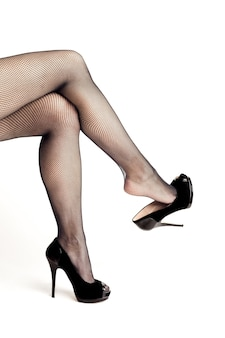 Sexy vrouwelijke benen in hoge hak zwarte schoenen en visnetkousen geïsoleerd op een witte achtergrond