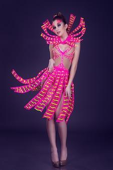 Sexy vrouwelijke disco danseres poses in uv-kostuum