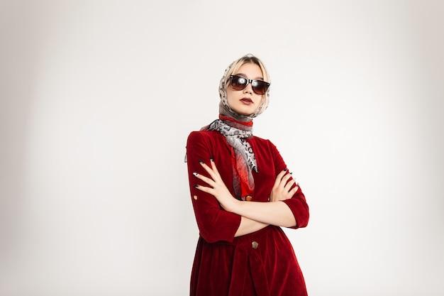 Sexy zakelijke modieuze jonge vrouw in fashion zonnebril in bordeauxrode elegante jurk met vintage luipaard sjaal op hoofd poseren binnenshuis indoor