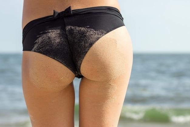 Sexy zandige vrouwenbillen op tropische strandachtergrond dichtbij oceaan.